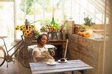 Female Florist Enjoying Coffee Break At Table In Flower Shop