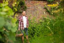 Portrait Confident Man With Basket At Brick Wall In Summer Garden