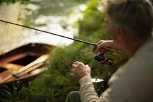 Man Fly Fishing At Riverbank