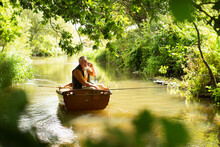 Man Talking On Smart Phone And Fly Fishing In Boat On Sunny River