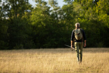 Man With Backpack And Fly Fishing Pole Walking In Rural Field