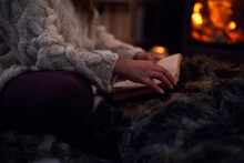Woman Reading Book On Blanket At Cozy Fireside