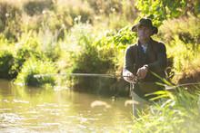 Man Fly Fishing At Sunny River