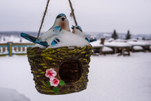 Hanging Planters With Clay Birds Covered With White Snow.
