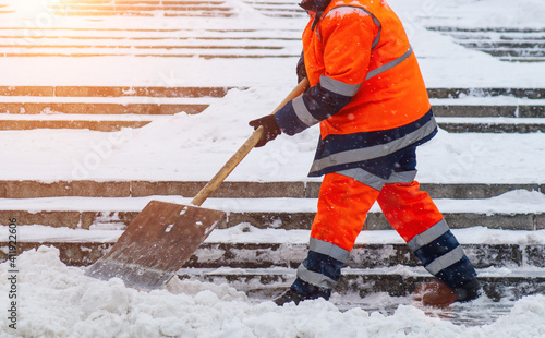 Obraz Snow removal. Worker clearing snow by shovel after snowfall. Outdoors - fototapety do salonu
