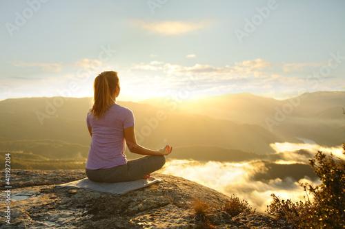 Obraz Woman meditating practicing yoga in the mountain - fototapety do salonu