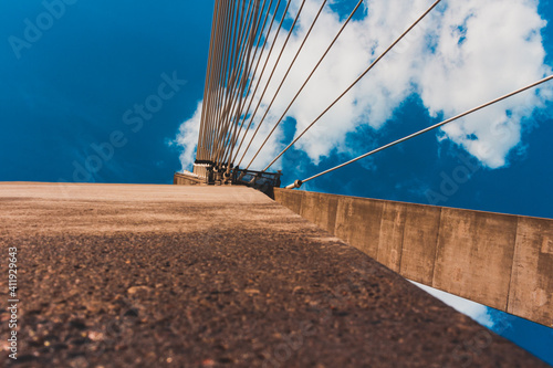 Fototapeta premium view from below on the part of the bridge with blue sky in background