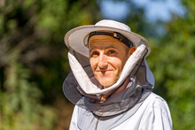 Head And Shoulders Portrait Of A Senior Beekeeper In White Protective Hat With Net. Blurred Background Of Green Trees. Closeup.