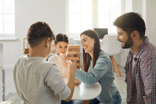 Family at the table playing board game. Happy young family plays with their children and take turns removing bricks from a wooden tower. Concept of development and logic games.