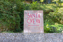Covadonga, Spain - September 4, 2020: Sign To The Holy Cave, Place Where Our Lady Of Covadonga Appeared To Pelayo. The Santa Cueva De Nuestra Senora De Cuadonga Is A Sanctuary Located In Asturias.