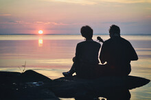 Guy And  Girl In Love Are Sitting On The Shore Of The Lake At Sunset And Sing A Song Under The Ukulele.