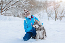 Alone Woman Wearing A Protective Mask Walks With Her Dog In The Winter Outdoors Due To The Covid-19 Coronavirus