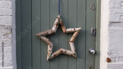 Fotografie, Obraz Star shape made out of silver birch tree branches hanging on door