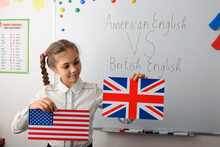 American English VS British English Concept. Cheerful Schoolgirl With American And British Flags In The Classroom, Learning Differences In Types Of English Languages