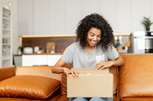 Positive Young African American Woman Sitting On The Couch With Carton Box On Laps, Feeling Curious About Ordered Item From An Online Store, Smiling Client Satisfied With Fast Courier Delivery Service