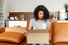 Disappointed Young African American Girl With Afro Hairstyle Sitting On The Couch With Carton Box And Feeling Upset And Confused With The Wrong Delivery From An Online Store, Or Bad Quality Purchase