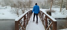 Person Snowshoeing Across A Snow Covered Bridge In The Middle Of A Snowstorm