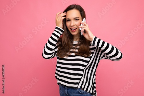 Obraz Photo shot of attractive emotional young woman speaking on the smartphone wearing striped sweater isolated over background with copy space looking at camera - fototapety do salonu