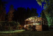 Wooden Gazebo On A Green Field In The Forest Against The Background Of The Night Blue Sky