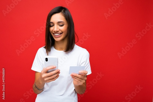 Photo shot of attractive positive good looking young woman wearing casual stylish outfit poising isolated on background with empty space holding in hand and using mobile phone messaging sms looking at