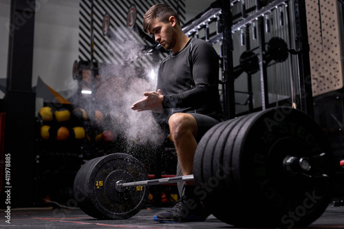 Obraz athlete man is getting ready for cross fit training. Cnfident powerlifter use talc preparing to raise heavy weight. At modern gym, fitness center - fototapety do salonu