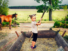 Girl Standing In A Wagon Holding A Pitchfork, Poland