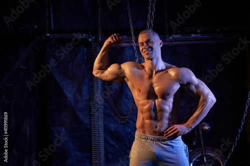 Canvas Print Young shirtless muscular man standing among metal chains, looking at camera, cop