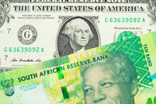 A Macro Image Of A Shiny, Green 10 Rand Bill From South Africa Paired Up With A Green One Dollar Bill From The United States.  Shot Close Up In Macro.