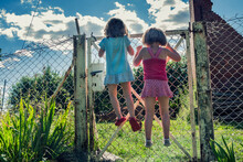 Rear View Of Two Girls Climbing On A Metal Fence, Poland