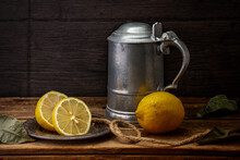 Lemons Next To A Metal Tankard On A Wooden Table