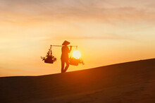 Woman Carrying Baskets Across A Sand Dune At Sunset, Mui Ne, Vietnam