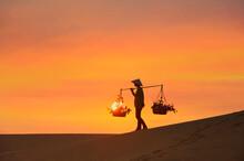 Woman Carrying Baskets Across A Sand Dune At Sunset, Mui Ne, Vietnam