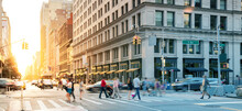 Crowds Of People In Motion Walking Across The Busy Intersection On 5th Avenue In Midtown Manhattan, New York City