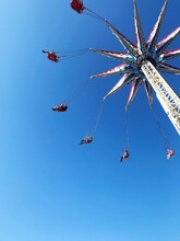 Low Angle View Of Chain Swing Ride Against Clear Blue Sky