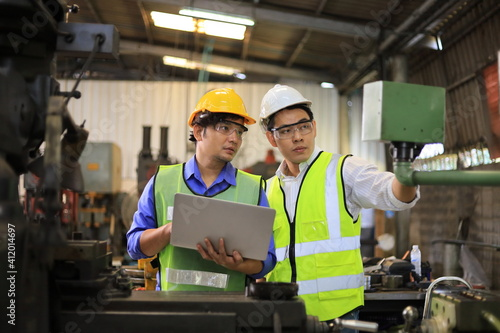Asian engineering manager and mechanic worker in safety hard hat and reflective cloth using lathe machine inside the factory