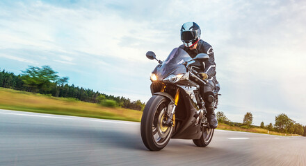 Man Riding Motorcycle On Road Against Cloudy Sky