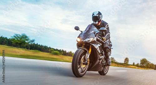 Fototapeta Man Riding Motorcycle On Road Against Cloudy Sky obraz