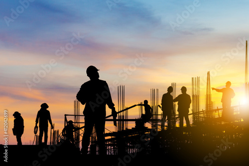 Obraz na plátně Silhouette of Engineer and worker on building site, construction site at sunset in evening time