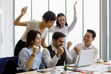 Group Of Five Diversity Businessmen, Two Men And Three Women, Looking At Notebook Computer Screen And Rise Hands With Excited And Happy.