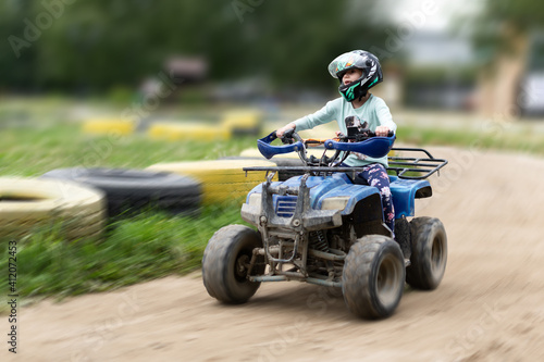 a child rides an ATV on the track Fototapeta