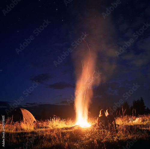 Obraz Beautiful view of night starry sky over grassy hill with camp tent, campfire and hikers. Young man and woman tourists having a rest near bonfire. Concept of hiking, night camping and relationship. - fototapety do salonu
