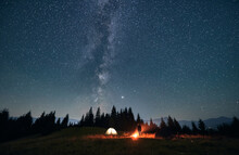 Silhouette Of Male Traveler Near Illuminated Camp Tent Under Beautiful Night Sky With Stars. Magnificent View Of Blue Starry Sky Under Grassy Hill. Concept Of Travelling, Hiking And Night Camping.