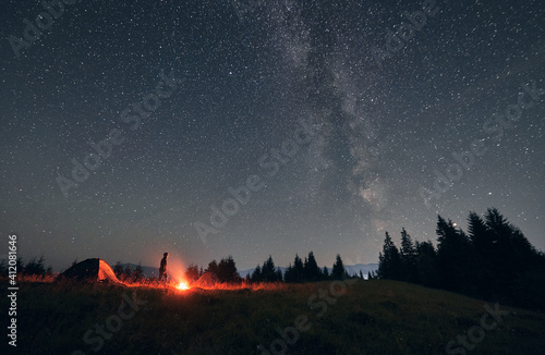 Obraz Male hiker standing near campfire and tent under beautiful night sky with stars. Magnificent view of blue starry sky and Milky way under grassy hill. Concept of travelling, hiking and night camping. - fototapety do salonu