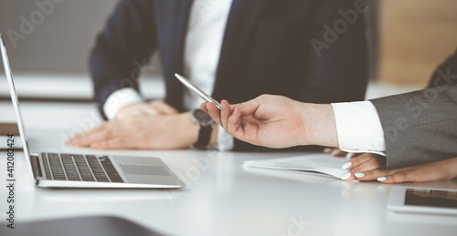 Fototapety, obrazy: Unknown businessmen and woman sitting, using laptop computer and discussing questions at meeting in modern office, close-up
