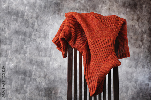 Obraz na plátně Women's wool knitted terracotta sweater casually thrown over the back of wooden chair against gray wall