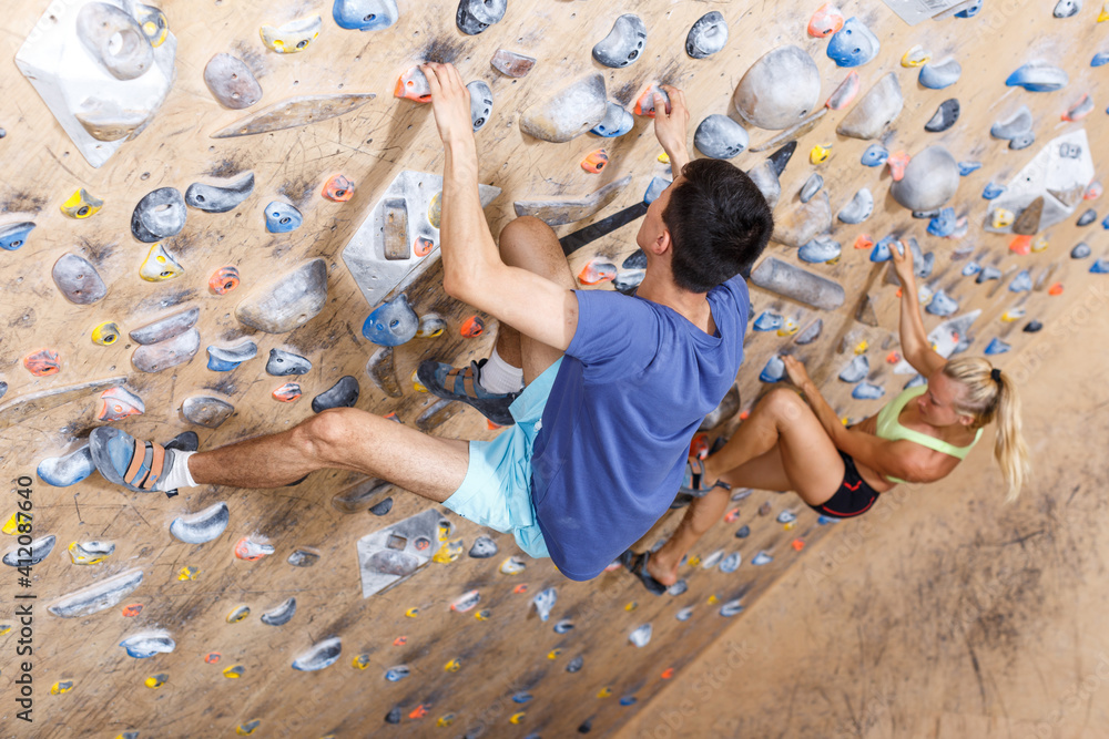 Fototapeta Sporty couple of climbers on joint workout training at bouldering gym