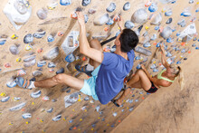 Sporty Couple Of Climbers On Joint Workout Training At Bouldering Gym
