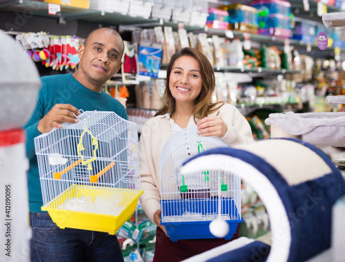 Cheerful couple of customers buying cage for bird in pet shop Fototapet