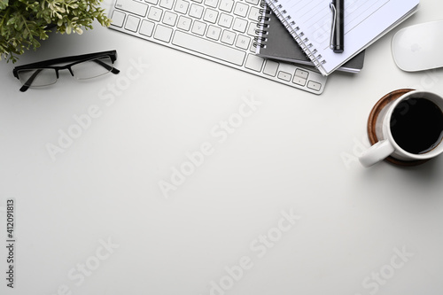 Fototapeta Top view of white office desk with notebook, wireless keyboard, coffee cup, glasses and copy space