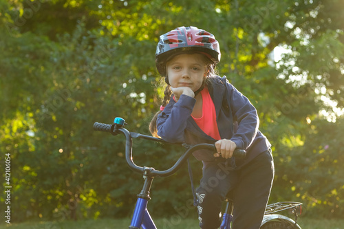 Fotografija Little girl learns to ride bike in park near home